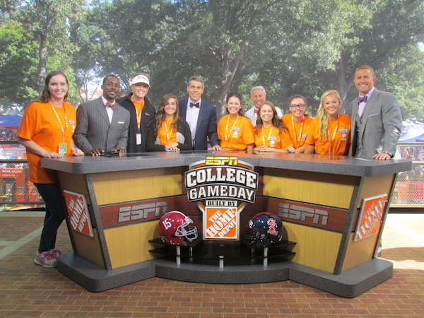 Student volunteers Catherine Carroon, Jimmy Anderson, Ashley Dunn, Tessa Poyner, Olivia Wells, and Chandler Marie Morgan posing with the ESPN College GameDay Anchors, including Desmond Howard, Chris Fowler, Lee Corso, and Kirk Herbstreit