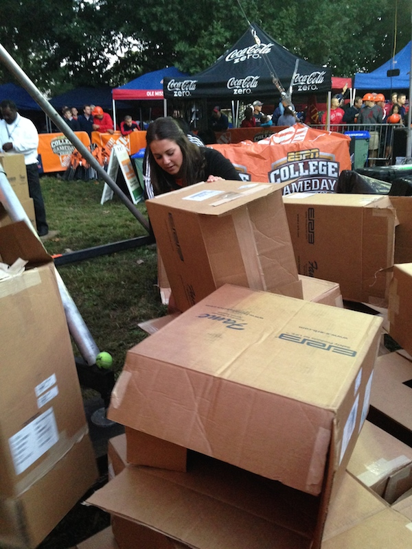 Student volunteer Ashley Dunn folding up boxes and boxes of College GameDay hats