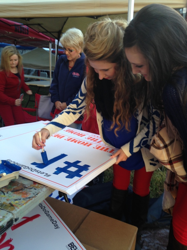 Ole Miss fans Jessie Jessinew and Reagan Pade paint their signs at the Home Depot tent station for College GameDay