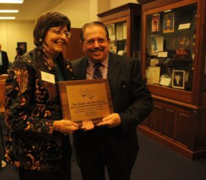 Dr. Julia Rhodes, dean of libraries, with the plaque she honored Ellis Nassour with for his exhibition.