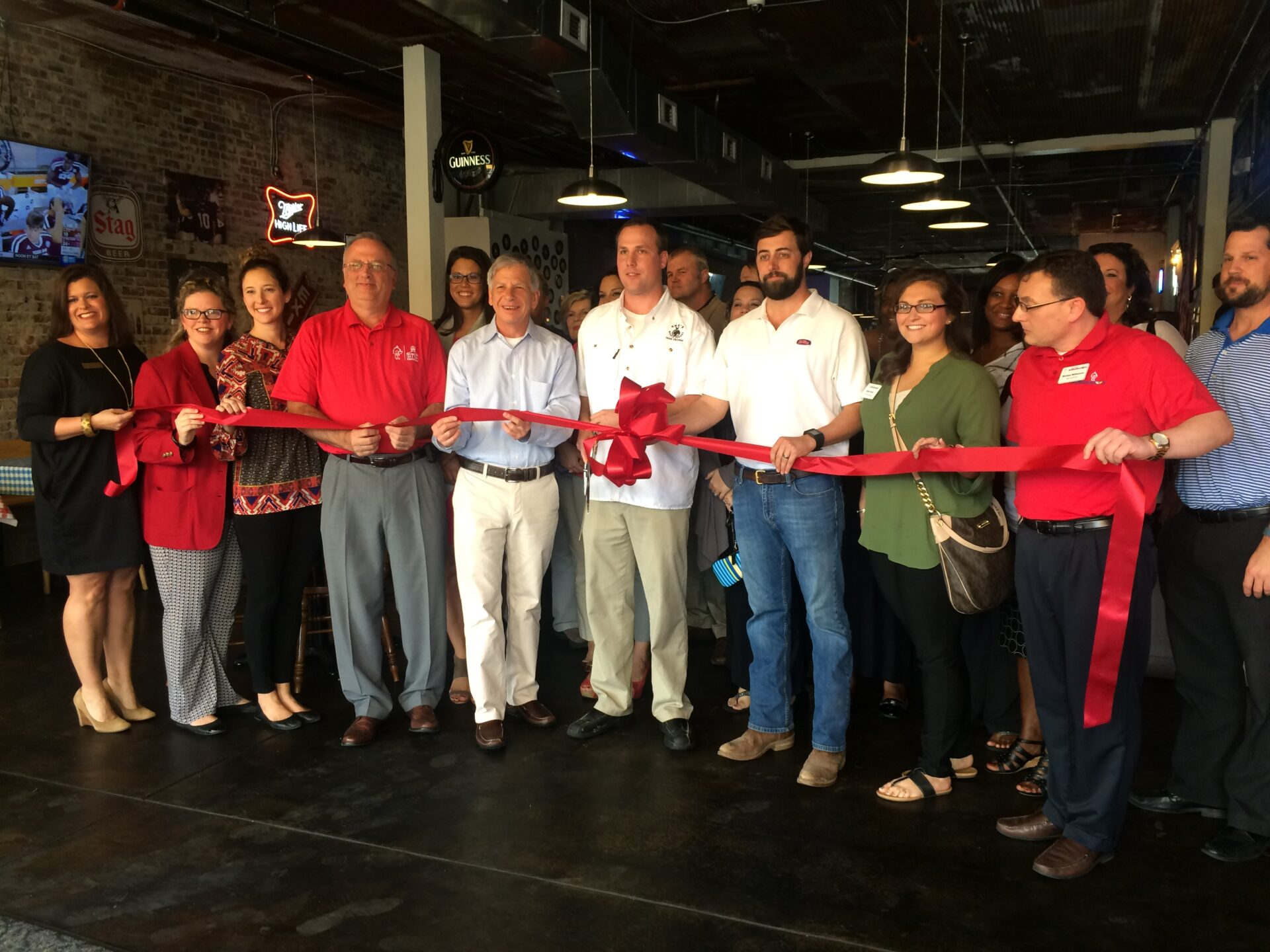 Chamber members and owners of Gus's Fried Chicken celebrate their first anniversary with a ribbon cutting.