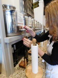 "Gina O'Connor fills ""happy-size"" bottles at J. Olive, Oxford's own purveyor of fine olive oils and balsamic vinegars."