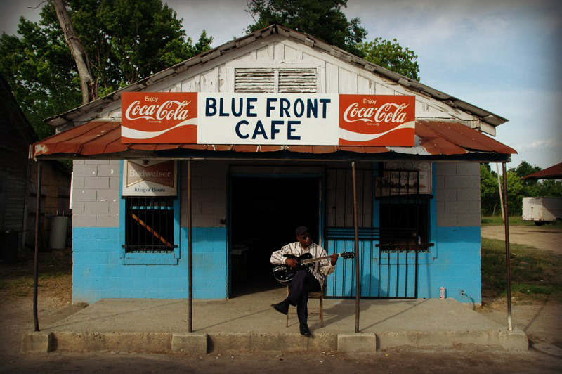 """Jimmy """"Duck"""" Holmes playing guitar outside the Blue Front Cafe."""