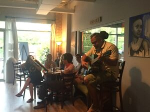 Dereck Brown plays the guitar at Mugg Cakes for Poeteats.