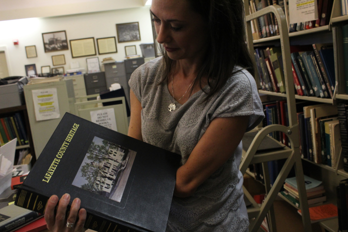 "Richardson looks at a book titled ""Lafayette County Heritage"" at the Lafayette County and Oxford Public Library."