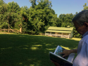 Ed Croom finds a picture of the now-dead pecan tree that once stood next to the stables at Rowan Oak.